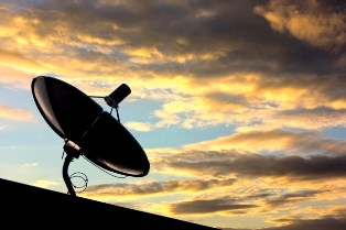 This graphic shows a typical roof top satellite dish against a beautiful sunset.