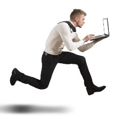 This image suggests the concept of the race to keep up with changing technology by featuring a running male office worker entering data on a laptop computer.""
