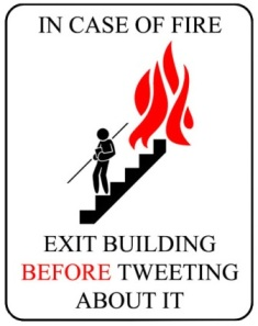 "This graphic shows a cartoon figure descending a fire-escape, pursued by flames. It features the legend ""In case of fire, exit building BEFORE tweeting about it""."""