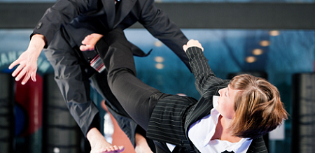Business woman performing kick boxing move on a competitor - defending her patch
